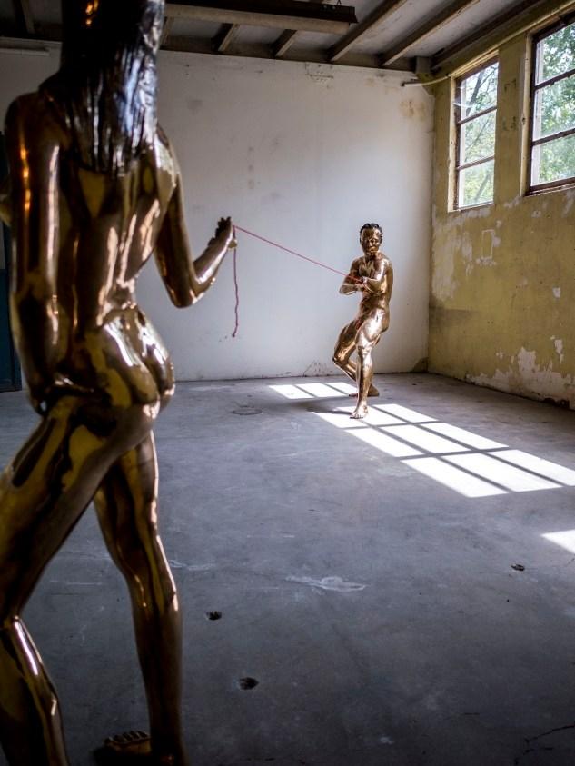 Pascale Marthine Tayou, Tug of war, 2007,Couple of bronze statues, red wool thread, Woman 160 cm, Man 155 cm © Sebastiano Pellion