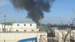 """A plume of smoke rises from the Sudanese quarter of """"The Jungle"""" in Calais as police begin demolishing the refugee camp.  Photo credit: Alexandra Vuillard."""