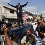 Wyclef Jean, center, greets supporters from the top of a vehicle after submitting the paperwork to run for president of Haiti in Port-au-Prince, Haiti, Thursday, Aug. 5, 2010.