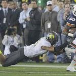 Auburn's Onterio McCalebb, right, carries the ball as Oregon's Spencer Paysinger dives after him