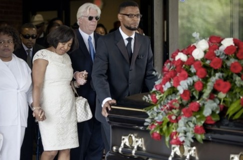 Donna Kelly Pratt, second from left, the mother of Chris Kelly, follows the casket of her son during his funeral recessional along with her husband James Pratte, second from right, Thursday, May 9, 2013, in Atlanta