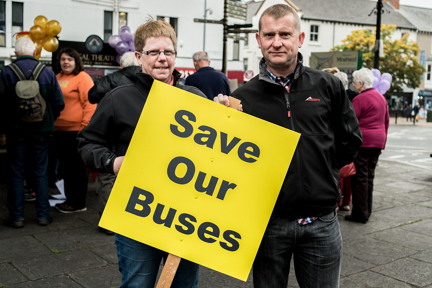 Couple hold up a yellow Save Our Buses placard