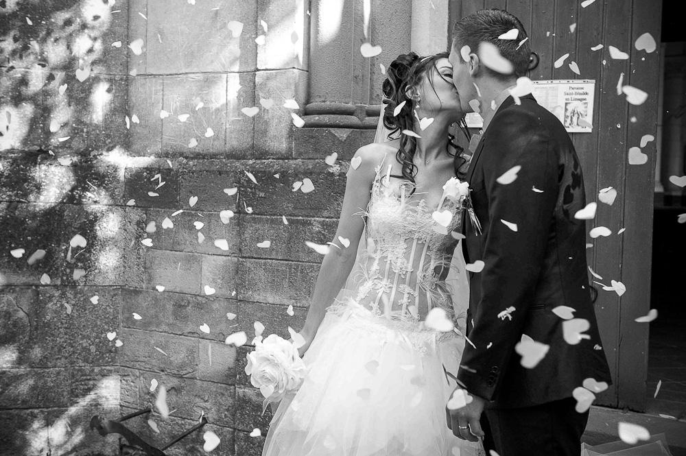 Les mariés s'embrassent à la sortie de l'eglise sous une pluie de petits coeurs blancs.