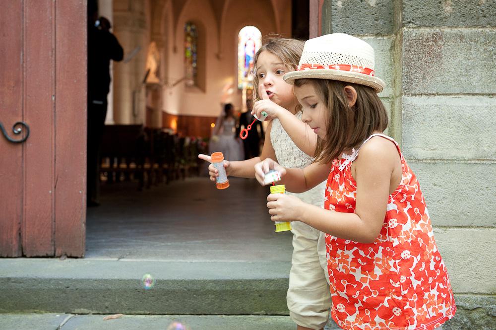 Deux petites filles font des bulles avant que les mariés sortent de l'eglise.