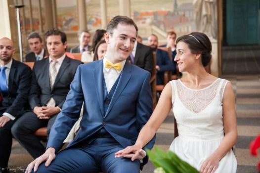 Regard et sourire complices des mariés qui se tiennent la main, pendant le mariage civil à la mairie de clermont-ferrand.