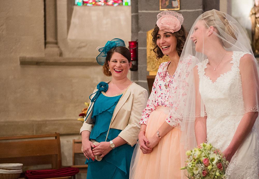 Complicité entre la mariée et les demoiselles d'honneur qui rient aux éclats durant la cérémonie de mariage religieux à l'église de chamalières.