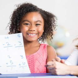 Joyful little girl holding her homework and looking at camera