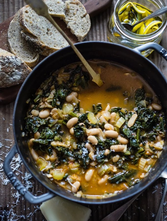A flavorful hearty stew from Tuscany, called Ribollita with Cannellini beans, lacinato kale, and vegetables, served with crusty bread, drizzled with a Lemon Rosemary Garlic Oil. | www.feastingathome.com