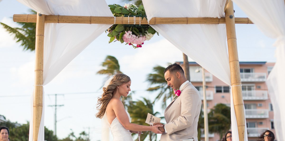 groom reads his wows to his bride on their key west beach wedding ceremony