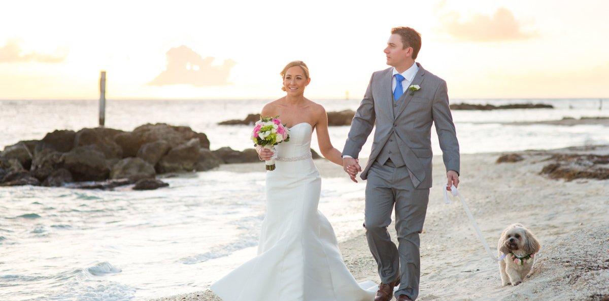 photo of bride and groom walking their dog on key west beach