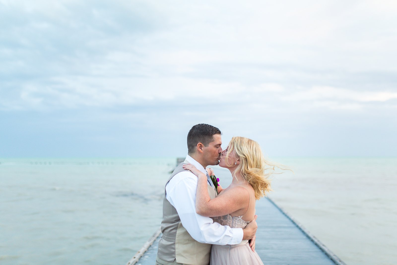 bride and groom kissing at the pier in key west, fl