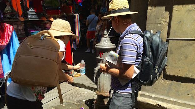 Turisti alla ricerca di acqua per combattere l'afa alla Loggia del Porcellino