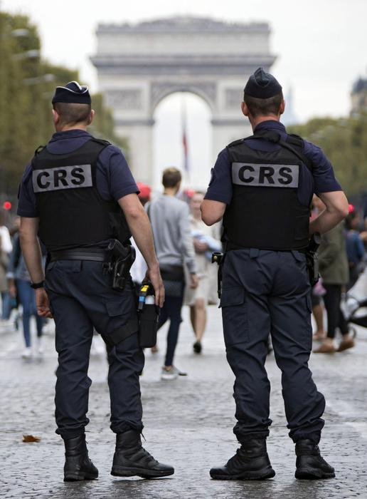 epa05555392 Police stand guard as pedestrians take to the street on the famous Champs-Elysee, free of its usual traffic as part of Paris' 'No Car Day', with traffic banned in sections of the city, and reduced to public transport vehicles only in other zones, in Paris, France, 25 September 2016. Paris mayor Anne Hidalgo had launched the first 'no car day' in september 2015, and plans to extend the initiative to every first Sunday of the month year-round. EPA/IAN LANGSDON