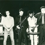 Pere Ubu - 1980, standing on stage. (l to r) Allen Ravenstine, Scott Krauss, Mayo Thompson, Tony Maimone, David Thomas.  Photo Credit: Rough Trade