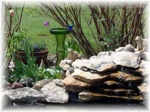 A side view of the green glass totem bird waterer