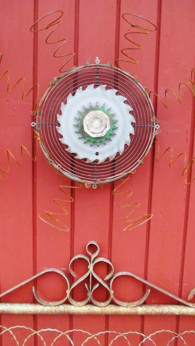 A fan cover, saw blade a gear, springs and a antique door knob