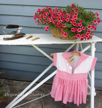Ironing board vignette includes a vintage iron, a tiny dress and a fresh pot of flowers