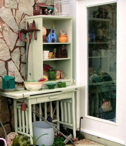 """Becky Norris says, """"This is my new (old) potting bench. It is put together from a flea market table, $1.00, old door, free, and discount shelf find, $20. Function and enjoyment...priceless!"""