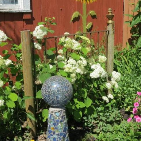 A mosaic stand and gazing ball shows craftsmanship and unique interest along the garden paths