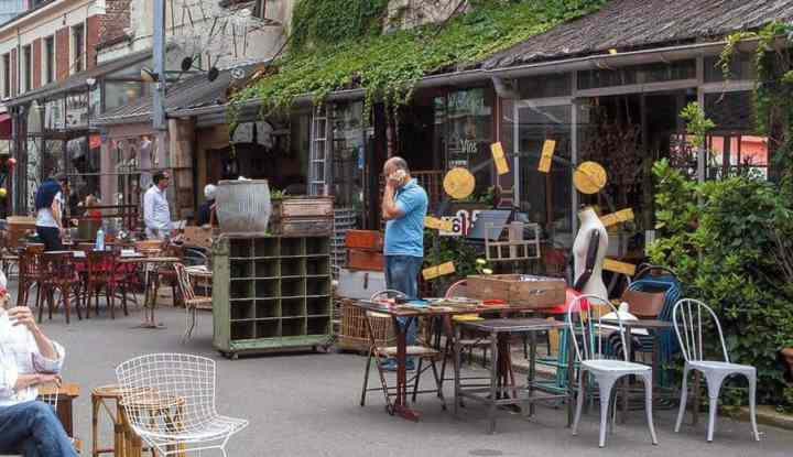 flea market merchants sitting outside their shop in st ouen flea market