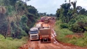Caminhões esperam parados na rodovia para continuar à trafegar.