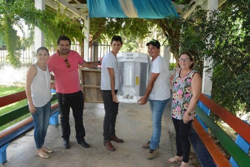 Secretaria de Educação e Prefeito entregando ar condicionado para escola