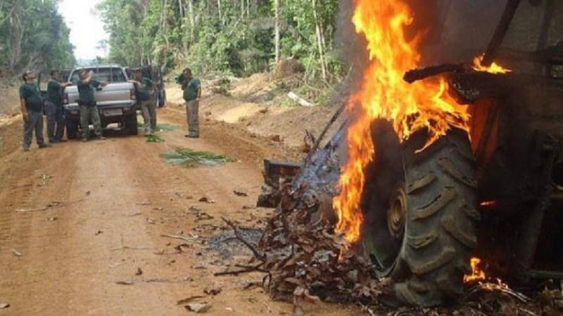 Agente do Ibama posa para foto à frente do trator capturado no interior da floresta(Foto Divulgação Internet)