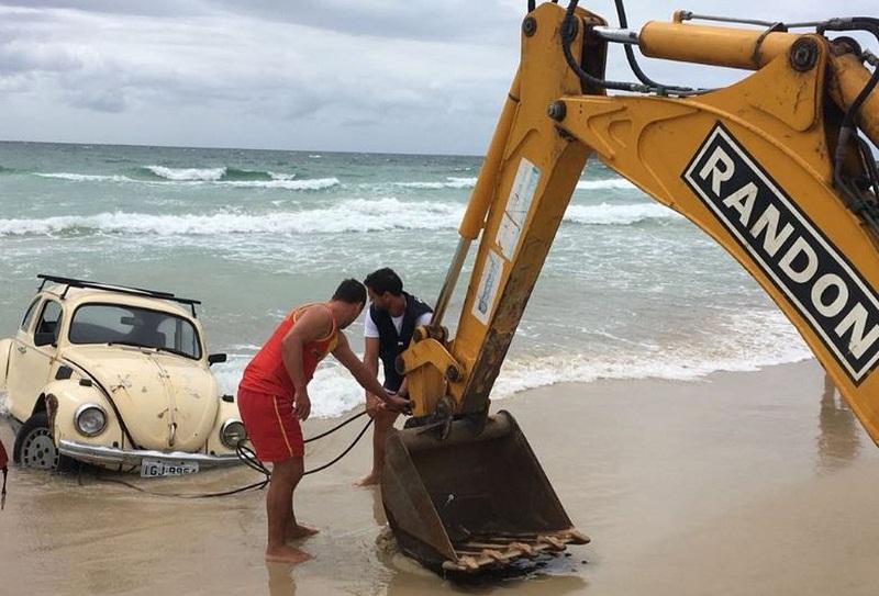 Uma retroescavadeira foi usada pela prefeitura para tirar carro do mar (Foto: Prefeitura de Florianópolis/divulgação)