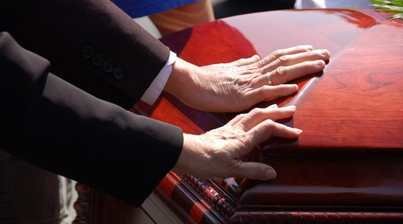 2 hands touching a closed wooden casket.  Farewell to a loved one.