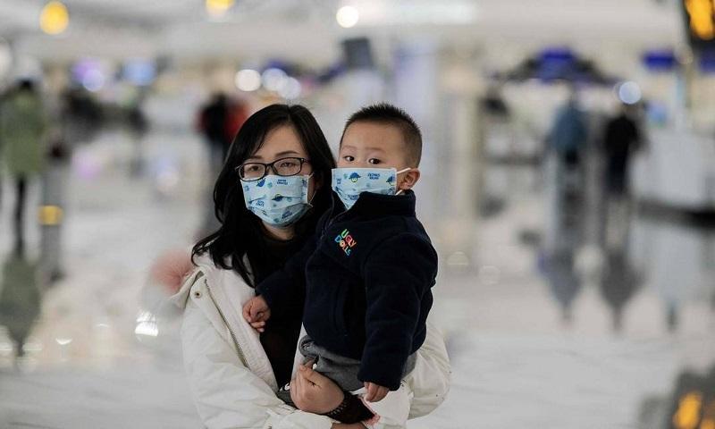 Uma mulher com uma criança no colo usa máscaras de proteção no aeroporto internacional de Daxing, em Pequim. Número de mortes causadas pelo coronavírus na China chegou a 17 nesta quarta-feira Foto: NICOLAS ASFOURI / AFP