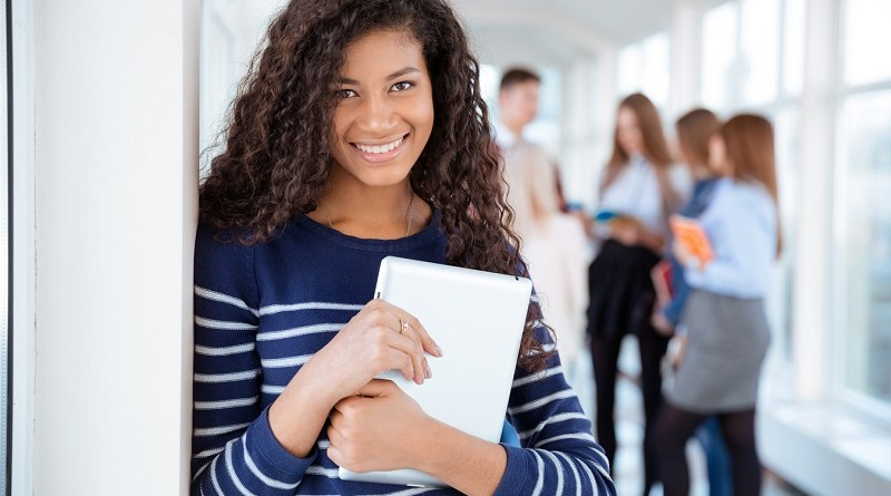 Portrait of a smiling female student standing in university hall with classmates on a background