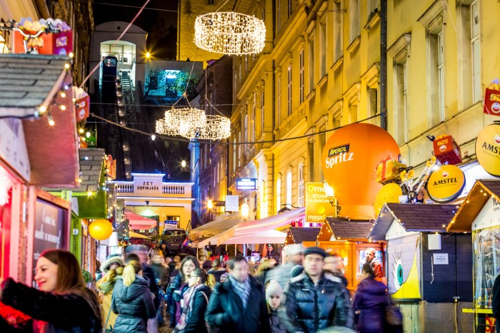 "Tomiceva Street is a small street leading up to the city's funicular. During Advent, it transforms into ""Fuliranje,"" which means ""fooling around."" Here, you'll find kiosks representing food cultures from all over the world. (Photo credit: The Zagreb Tourist Board and Julien Duval)"