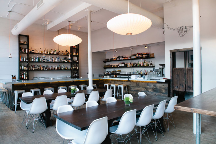 Opened in 2013 by Andrew Volk, this Scandinavian-inspired cocktail bar fittingly features a clean and minimal aesthetic with white walls, communal tables, and Herman Miller pendant lighting and chairs. (Photo credit: Meredith Perdue)