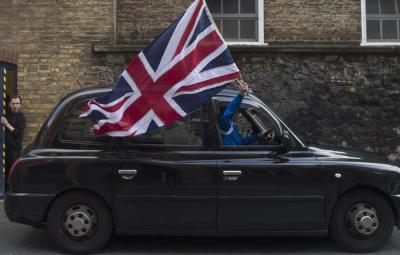 epa05387144 A London Black taxi driver flies a British flag as he drives through a street in central London, Britain, 24 June 2016. Britons in a referendum on 23 June have voted by a narrow margin to leave the European Union (EU). Media reports on early 24 June indicate that 51.9 per cent voted in favour of leaving the EU while 48.1 per cent voted for remaining in.  EPA/HANNAH MCKAY