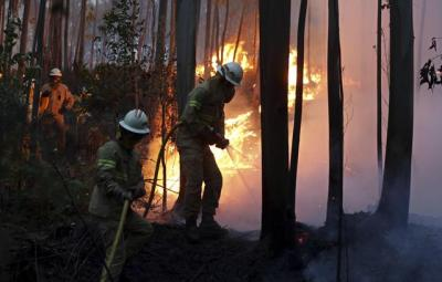 Firefighters of the Portuguese National Republican Guard work to stop a forest fire from reaching the village of Avelar, central Portugal, at sunrise Sunday, June 18 2017. A number of people have been killed in forest fires in central Portugal, many of them trapped in their cars as flames swept over a road Saturday evening. (ANSA/AP Photo/Armando Franca) [CopyrightNotice: Copyright 2017 The Associated Press. All rights reserved.]