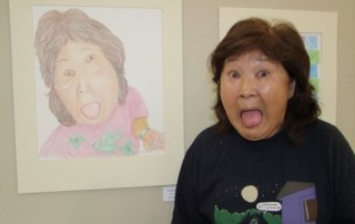 """Lori Suganuma with her color pencil drawing, """"In Your Face"""""""