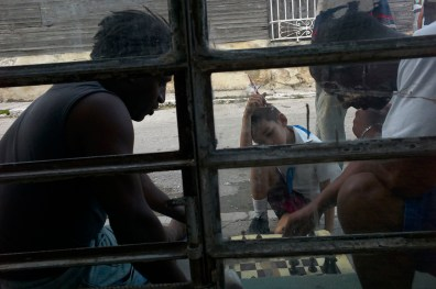 Kid watching adults play checkers on the street. Regla, November, 2013.