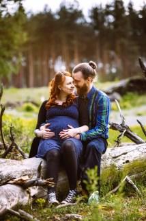 Paar sitzt im Wald für ein Babybauchshooting.