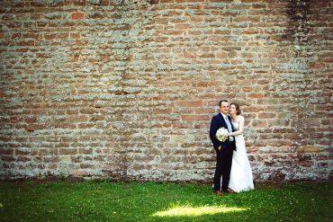 Verliebtes Hochzeitspaar auf großer Wiese.