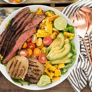 This Mexican Grilled Flank Steak Salad with Honey Lime Dressing has a smokey spiced grilled flank steak, charred corn, grilled onions, creamy avocado and a zingy honey lime dressing. Quick to make inside on the stove or outside on the grill!