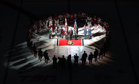 OTTAWA, ON - OCTOBER 25: In a coordinated tribute with NHL games in Montreal and Toronto to honor Canadian soldiers who lost their lives this past week, members of the Ottawa Senators and the New Jersey Devils stand together at center ice for the national anthems at Canadian Tire Centre on October 25, 2014 in Ottawa, Ontario, Canada. (Photo by Andre Ringuette/NHLI via Getty Images) *** Local Caption ***