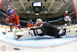Russia's Andrei Svechnikov #14 gets a first period goal against Latvia's Mareks Mitens #30 while Regnars Udris #4 and Russia's Pavel Dyomin #8 looks on during preliminary round action at the 2016 IIHF Ice Hockey U18 World Championship. (Photo by Matt Zambonin/HHOF-IIHF Images)