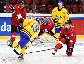 Sweden's Alexander Nylander #19 gets a shot off on Switzerland's Gauthier Descloux #29 with pressure from Noah Rod #26 during preliminary round action at the 2016 IIHF World Junior Championship. (Photo by Matt Zambonin/HHOF-IIHF Images)