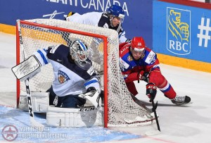 Russia's Alexander Dergachyov #25 wraps the puck around the net to get a shot off on Finland's Kaapo Kahkonen #1 with pressure from Finland's Niko Mikkola #7 during gold medal game action at the 2016 IIHF World Junior Championship. (Photo by Matt Zambonin/HHOF-IIHF Images)