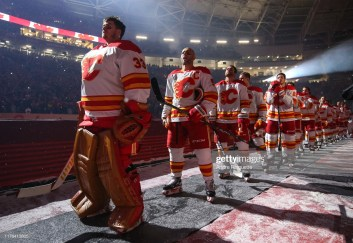 REGINA, SK - OCTOBER 26: David Rittich #33 of the Calgary Flames listens to the Canadian national anthem before taking on the Winnipeg Jets during the 2019 Tim Hortons NHL Heritage Classic at Mosaic Stadium on October 26, 2019 in Regina, Saskatchewan, Canada. (Photo by Andre Ringuette/NHLI via Getty Images)