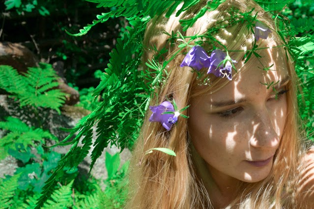 Pastel haired fairy with straight eyebrows and crown of wild flowers