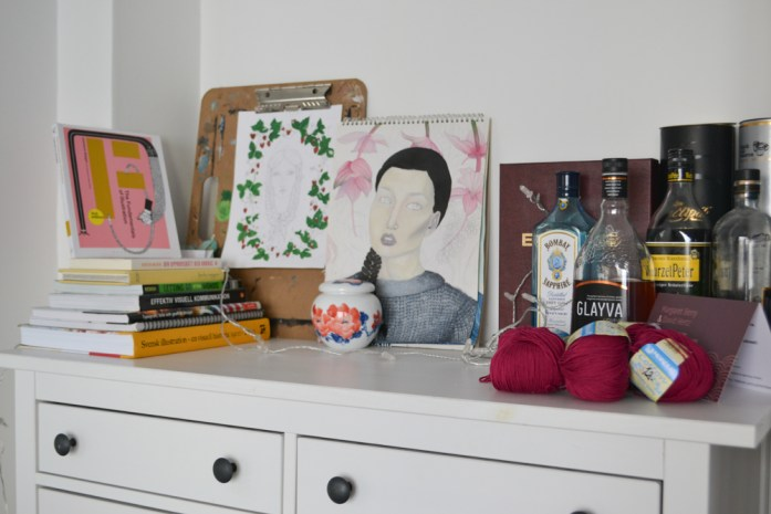 cupboard with art and book stack