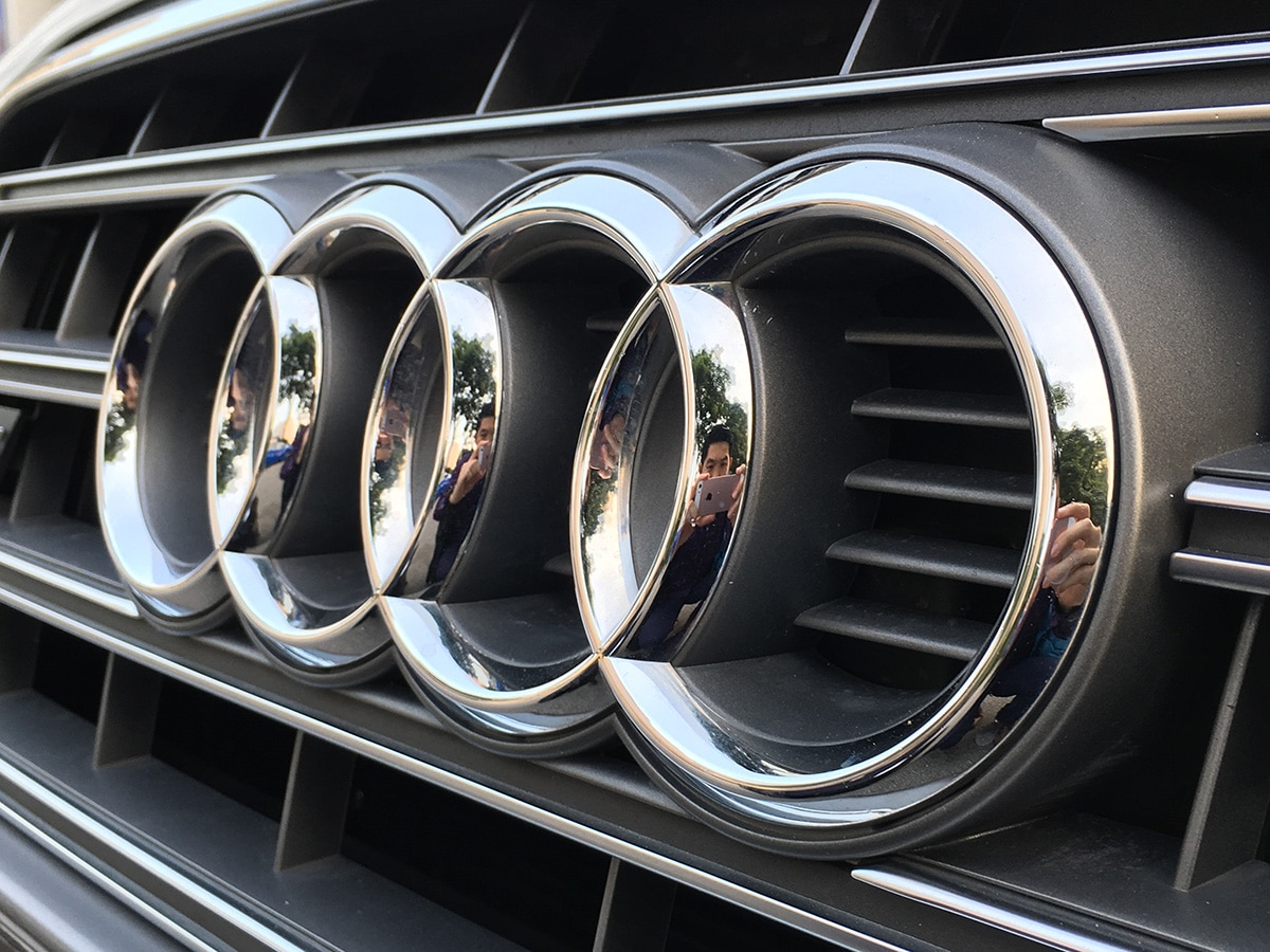 Audi logo on a car with reflections of the photographer