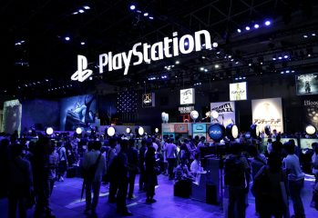 Attendees walk past a Sony Computer Entertainment Inc. booth displaying a PlayStation logo at the Tokyo Game Show 2015 at Makuhari Messe in Chiba, Japan, on Thursday, Sept. 17, 2015. There will be record attendance at this year's show with 473 vendors, including more than half from abroad, as of Sept. 1, according to organizers.  Photographer: Kiyoshi Ota/Bloomberg