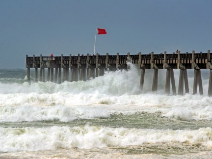 The red flag blows in the wind as waves crash around the Pensacola Beach Pier during tropical storm Cristobal Sunday, June 7, 2020.